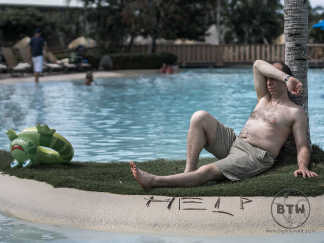 "Aaron laying next to a pool in Costa Rica, with the word ""HELP"" spelled out in front of him"